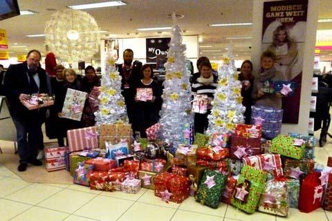 Mitarbeitende der Caritas und Alexander Bischoff (Adler, 5. von links) mit den 80 Geschenken der Adler-Kunden