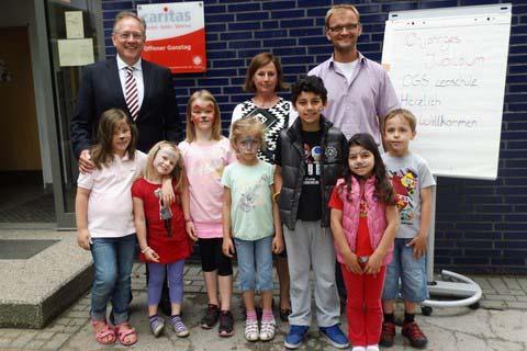 Vorstand Hans-Peter Benstein (links)), OGS-Leitung Margret Banken-Konrad und Schulleiter Mathias Flechtner freuen sich mit den Kindern